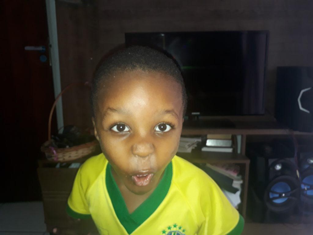 Ceci est le visage d'un enfant en confinement mais qui danse et chante sans savoir ce qu'il raconte